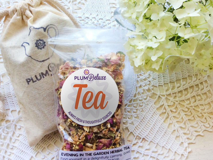 A package of Plum Deluxe loose leaf tea, a muslin bag stamped with a teapot, and a bunch of white hydrangea are arranged on a white lace cloth.