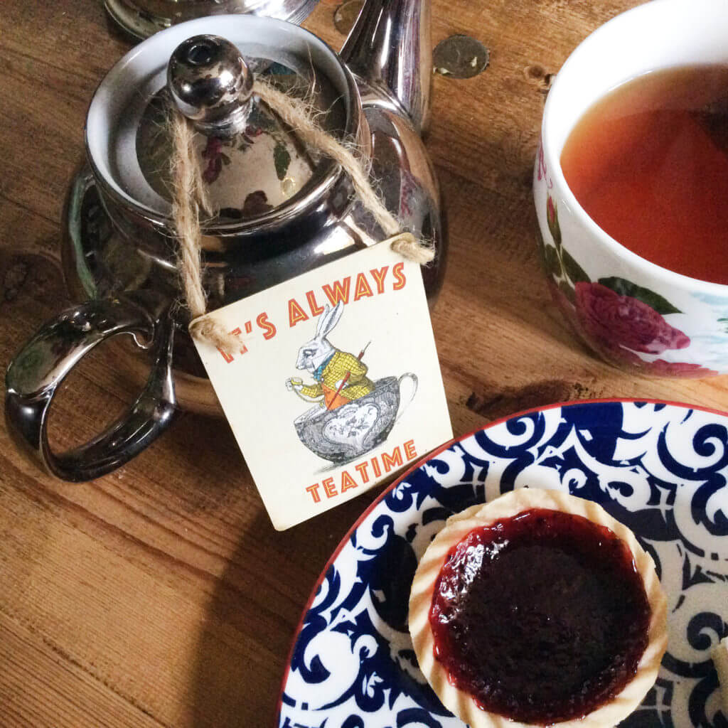 "A silver teapot with a sign that says ""It's Always Teatime"" sits next to a mug full of a tea and a jam tart on a blue and white plate."