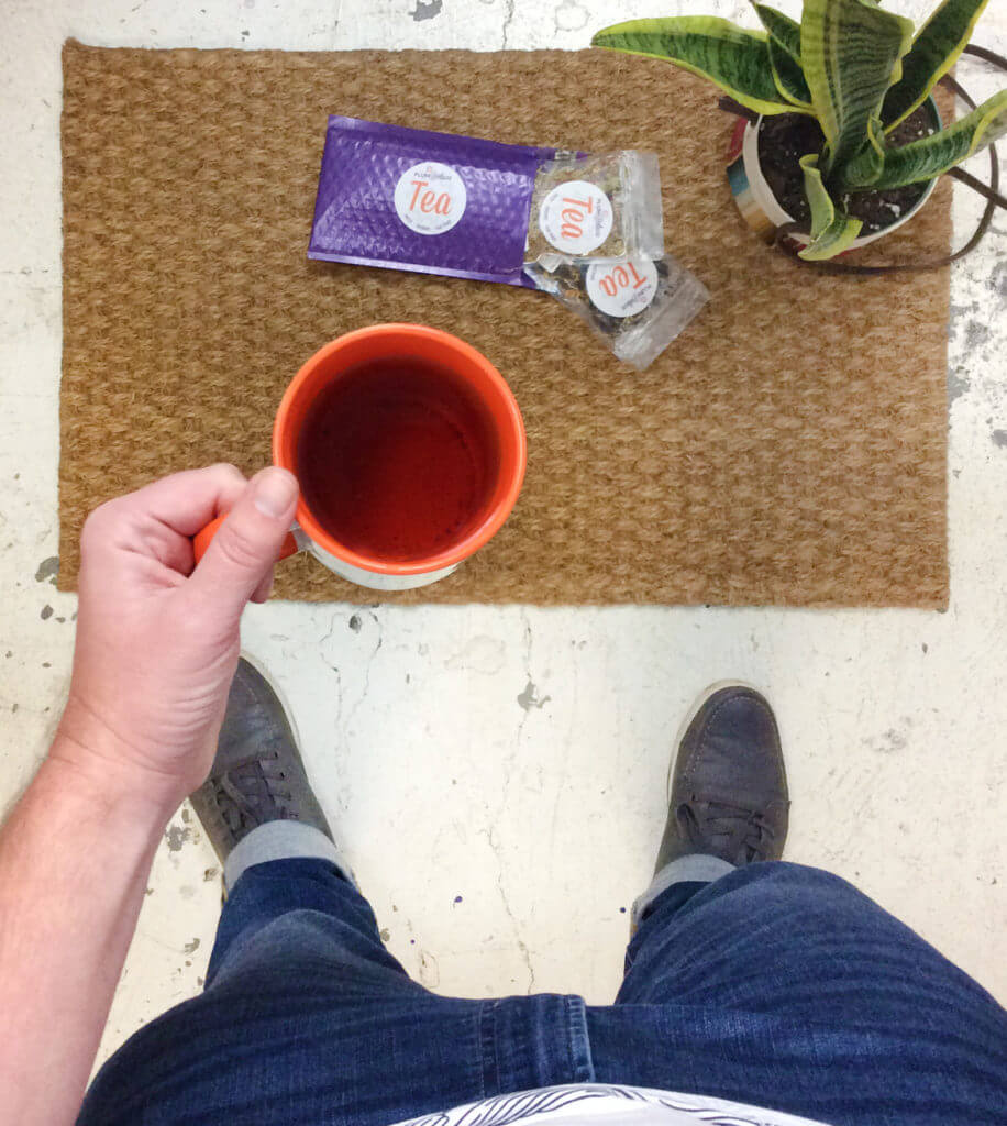 A person in jeans and sneakers holds an orange mug full of tea while standing next to a welcome mat full of loose leaf tea mail.
