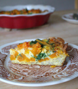 side view of a slice of squash quiche on a brown and white toile plate