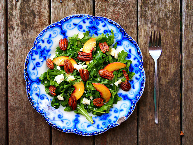overhead view of an arugula salad with candied pecans, peaches, and honey citrus dressing on a blue and white plate