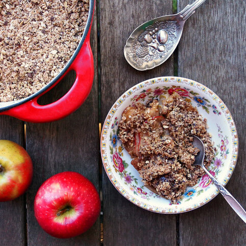 overhead view of a serving of baked apple casserole with chocolate oat topping in a floral dish, surrounded by red apples and a silver spoon on a wooden surface