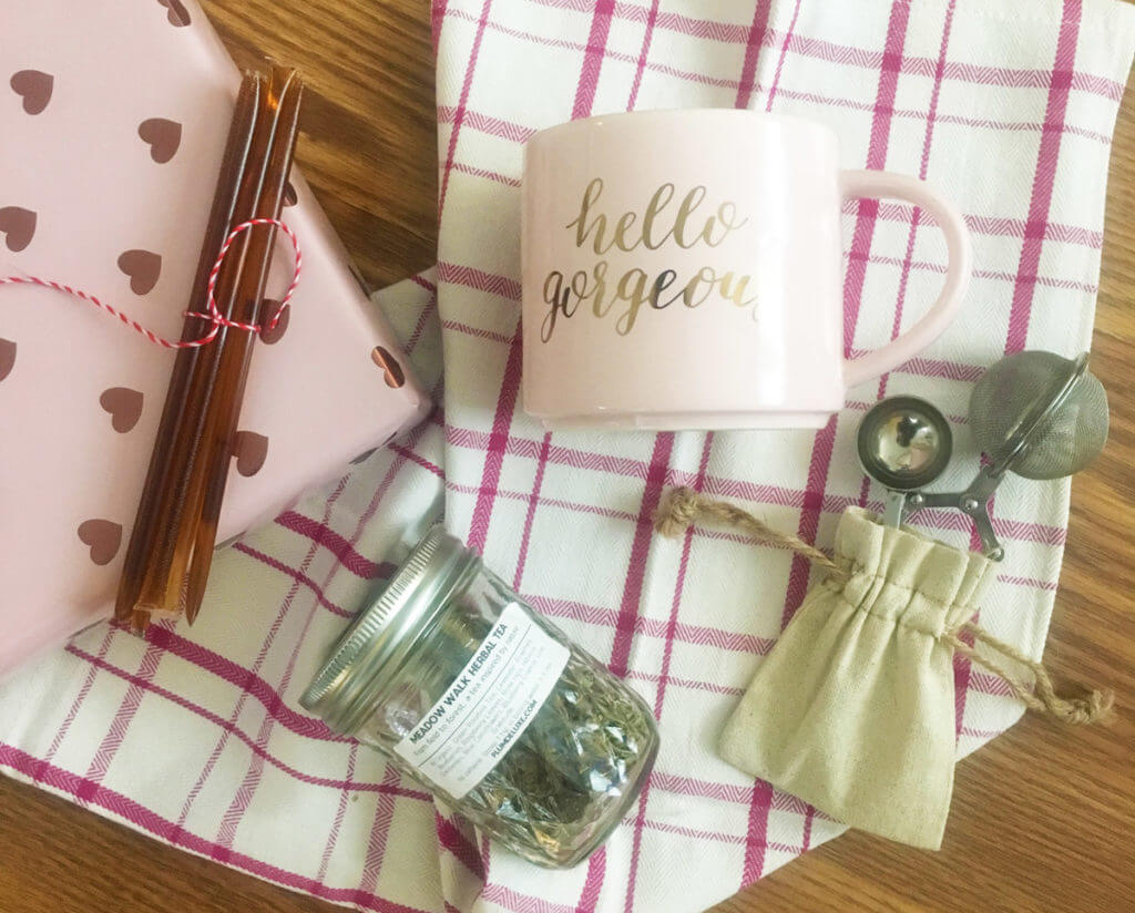 overhead view of gifts for people who like tea, including a mug, tea infuser, tea towel, jar of loose leaf tea, and honey sticks