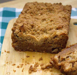 a loaf of apple bread with crumb topping rests on a wooden cutting board
