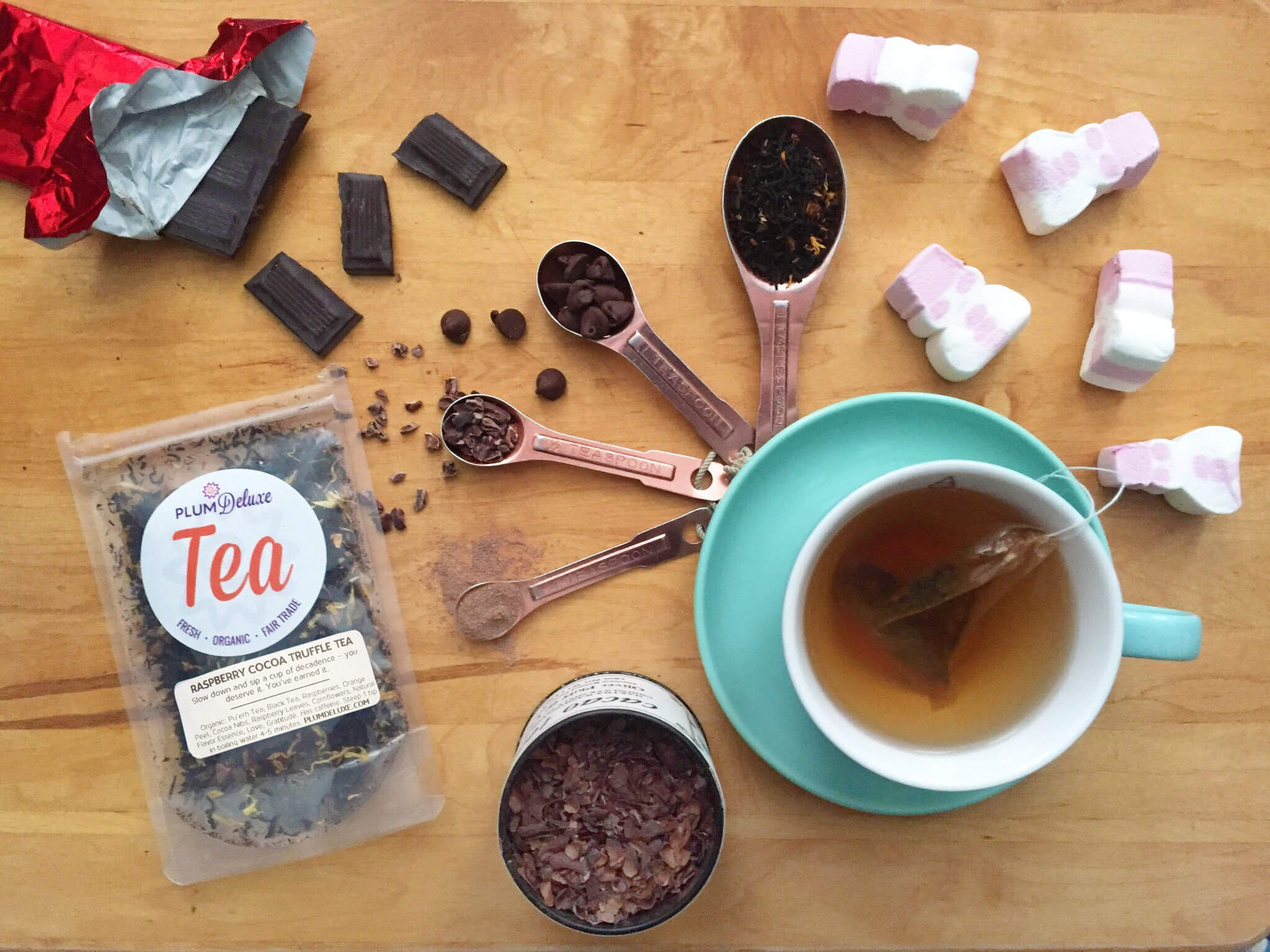 overhead view of tea in a blue teacup surrounded by chocolate, marshmallows, cacao nibs, and loose leaf tea