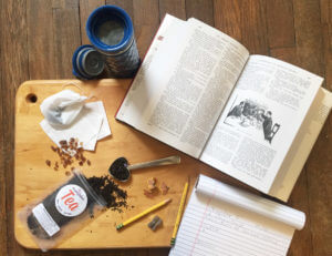 overhead view of loose leaf tea, sugar, and pencils on a wooden cutting board surrounded by paper, a book, and a travel mug