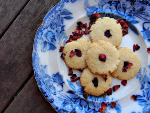 overhead view of five rosewater shortbread cookies on a blue willow plate, sprinkled with rose petals on a wooden table