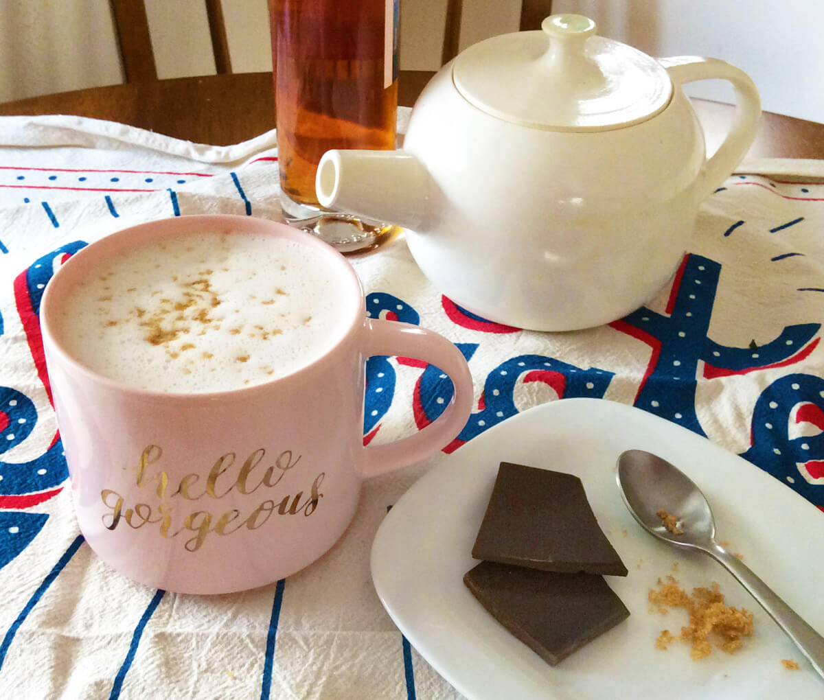 chocolate spiked hot tea in a pink Hello Gorgeous mug with a white teapot and chunks of chocolate
