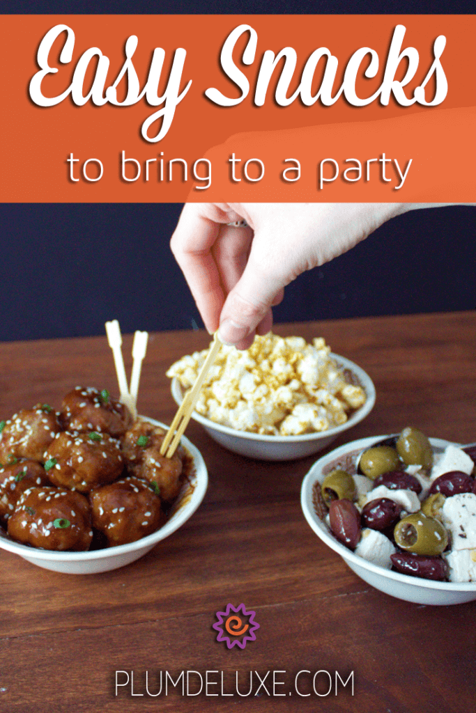 a hand reaches to skewer a cocktail meatball from a dish, while bowls of popcorn and olives with feta sit in the background