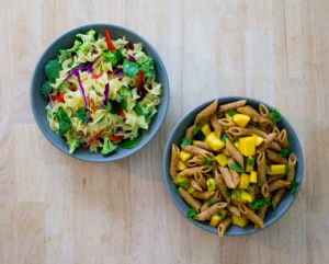 overhead view of two different pasta salads on a wooden table