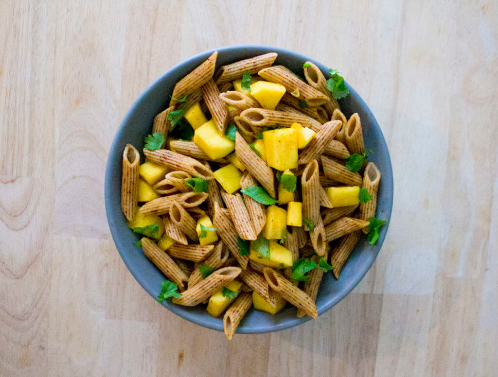 overhead view of a pasta salad with penne, mango, and chili