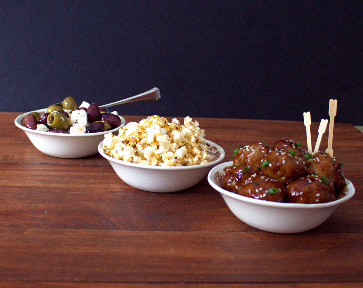 a bowl of cocktail meatballs covered in sauce sits in the foreground while spicy popcorn and marinated olives and cheese rest in the background