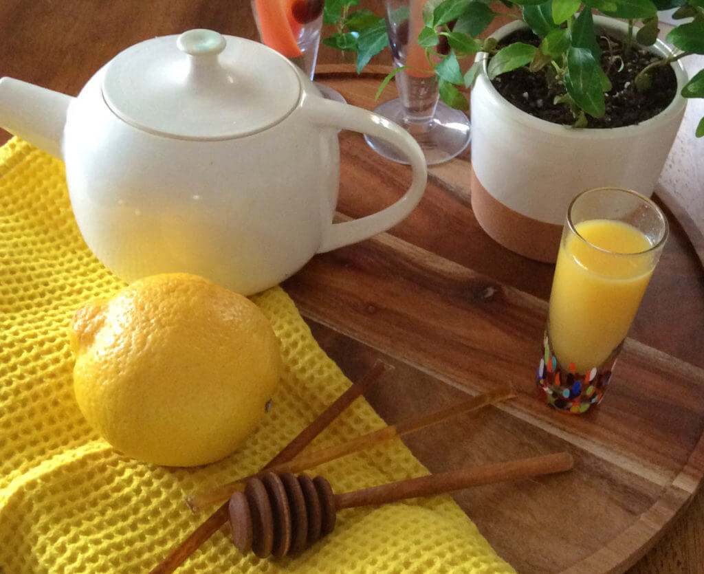 a spiked tea mimosa sits next to a white teapot and a lemon
