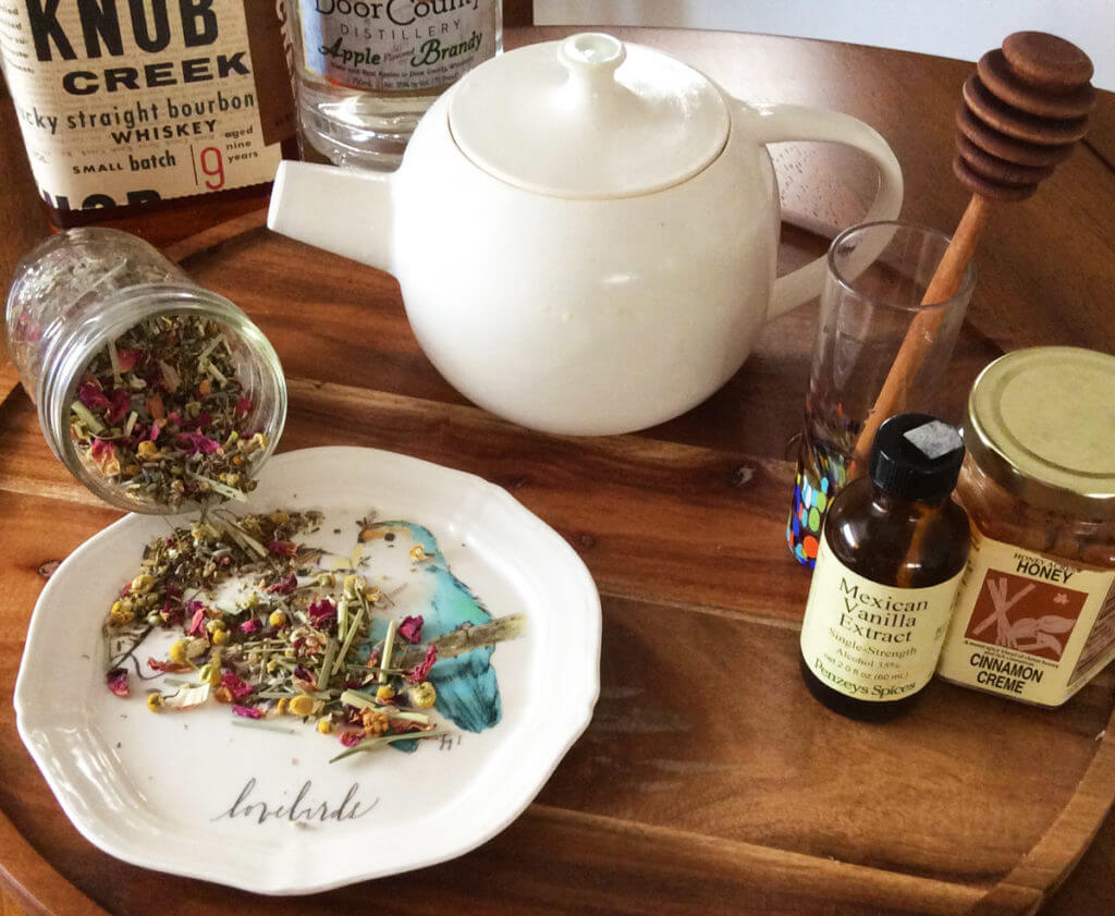 chamomile loose leaf tea spills out onto a plate in front of a white teapot and jars of honey