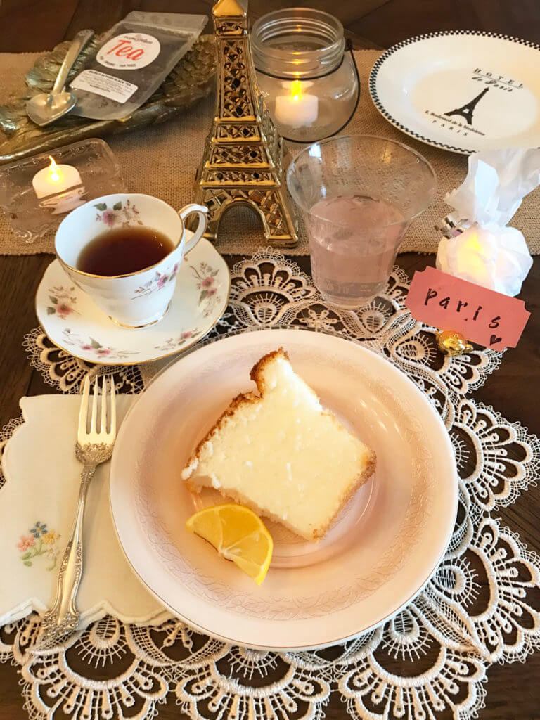 table setting for a Paris tea party with cake, tea, and party favors