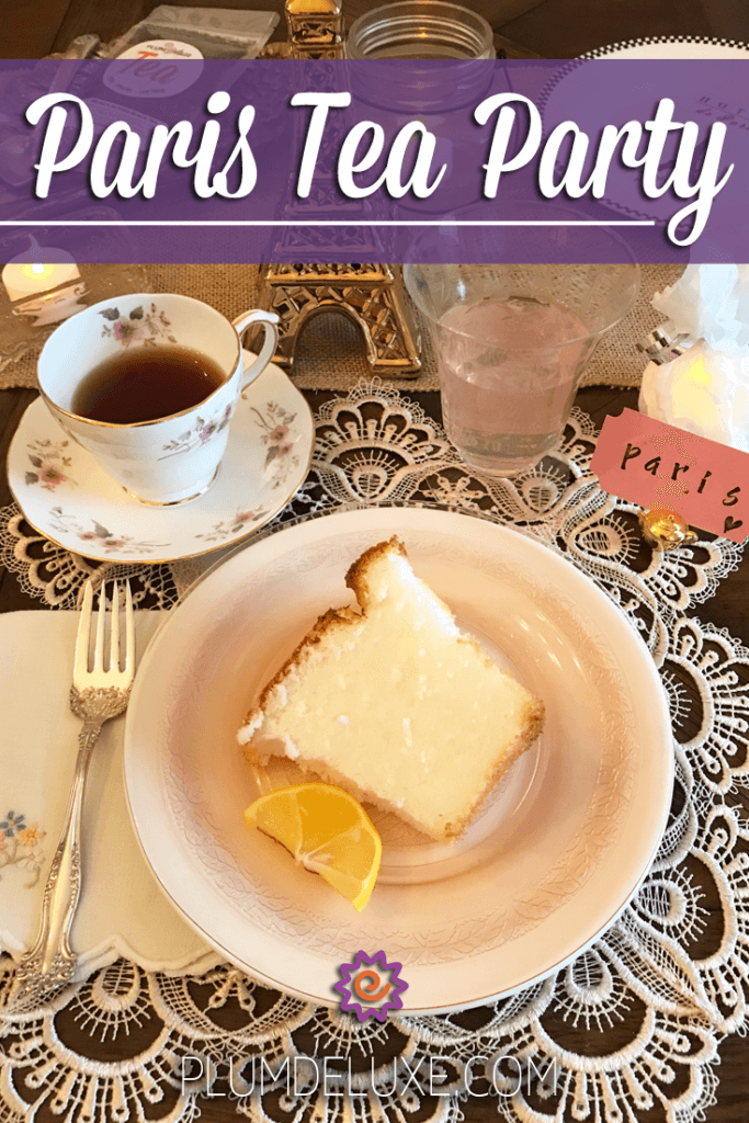 overhead view of a slice of angel food cake and cup of tea on a fancy paris themed place setting