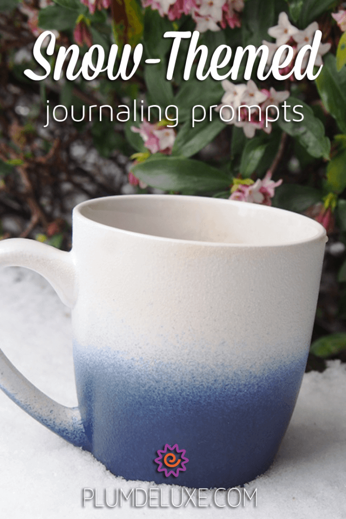 a blue and white mug of tea sits in the snow, with flowers in the background and the words Snow Themed Journaling Prompts