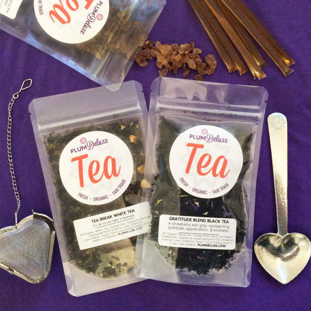 overhead view of two bags of loose leaf tea, a pewter heart tea scoop, a mesh heart tea infuser, honey sticks, and rock tea sugar