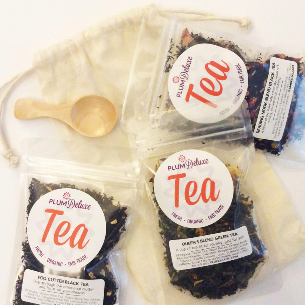 overhead view of three bags of loose leaf teas with a wooden tea scoop and linen gift bag