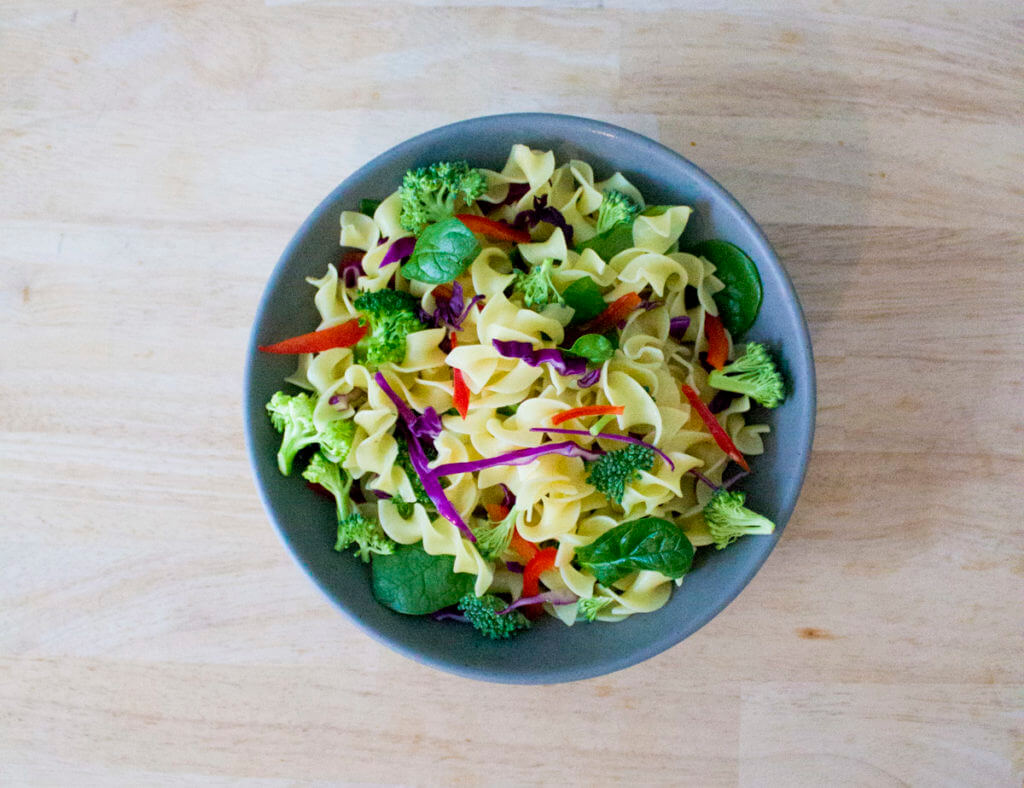 overhead view of a pasta salad with egg noodles, broccoli, vegetables, and orange ginger dressing