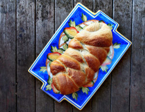 overhead view of a braided loaf of cardamom bread on a bright blue plate with wooden table background.