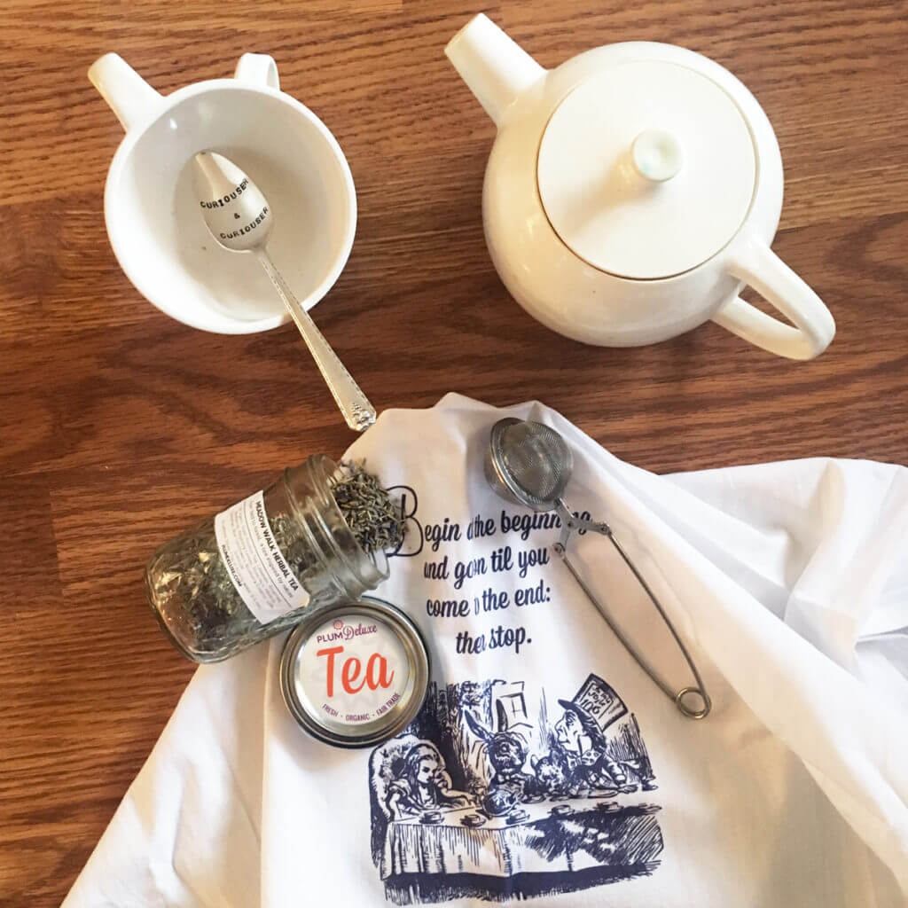 overhead view of a white tea pot and tea cup with silver tea spoon, Plum Deluxe loose leaf tea, infuser, and Alice In Wonderland tea towel.