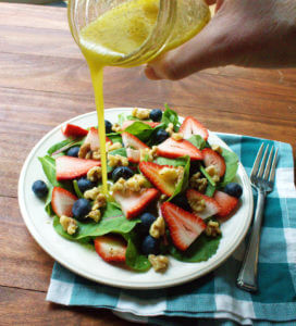 honey vinaigrette dressing is poured onto a strawberry blueberry salad with walnuts.