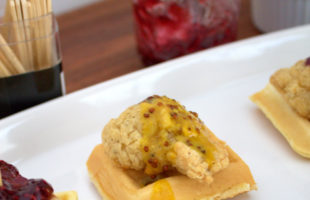 Closeup of a mini chicken and waffles appetizer with honey mustard dipping sauce.
