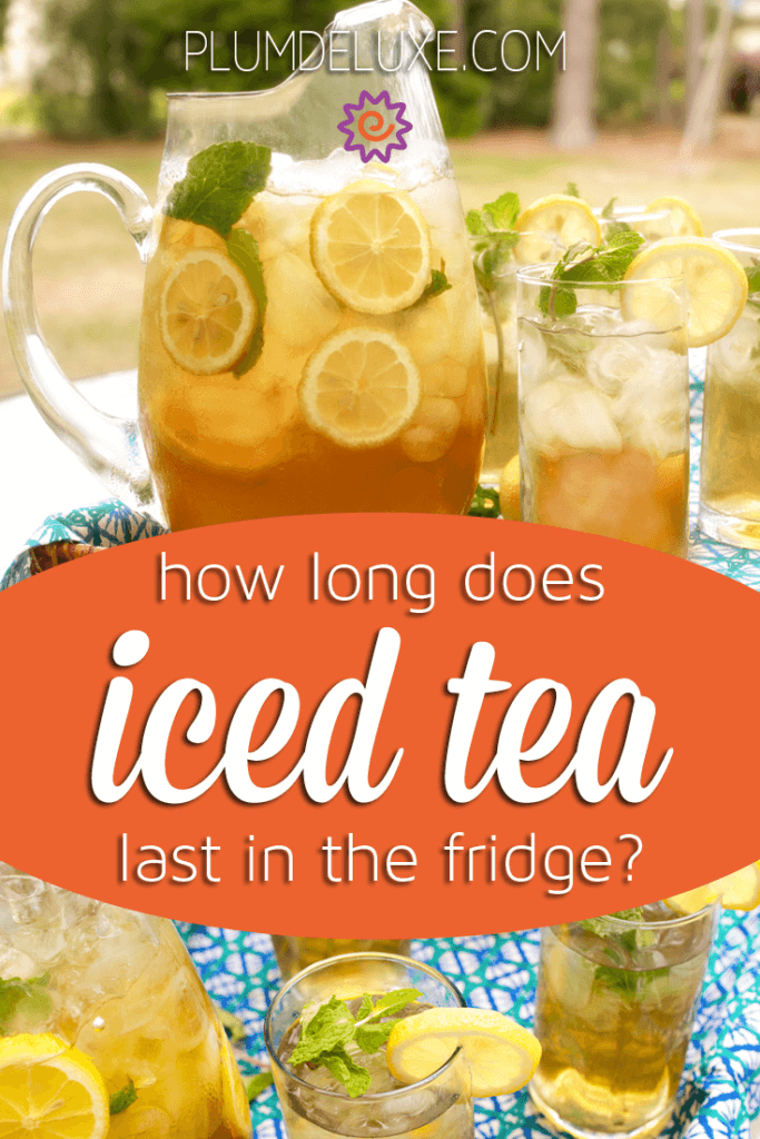 A pitcher of iced tea with lemon slices sits on a blue tablecloth with glasses of iced tea.