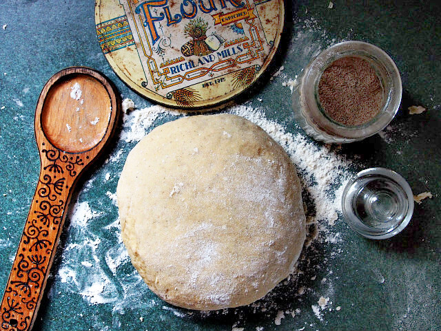 overhead view of a mound of cardamom bread dough with wooden spoon, cardamom, and flour.
