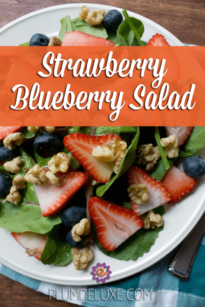 overhead closeup view of a salad with strawberries, blueberries, walnuts, greens, and honey vinaigrette dressing.