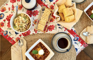 overhead view of an evening tea party table with turkey chili, cornbread, salad, crackers, and tea.