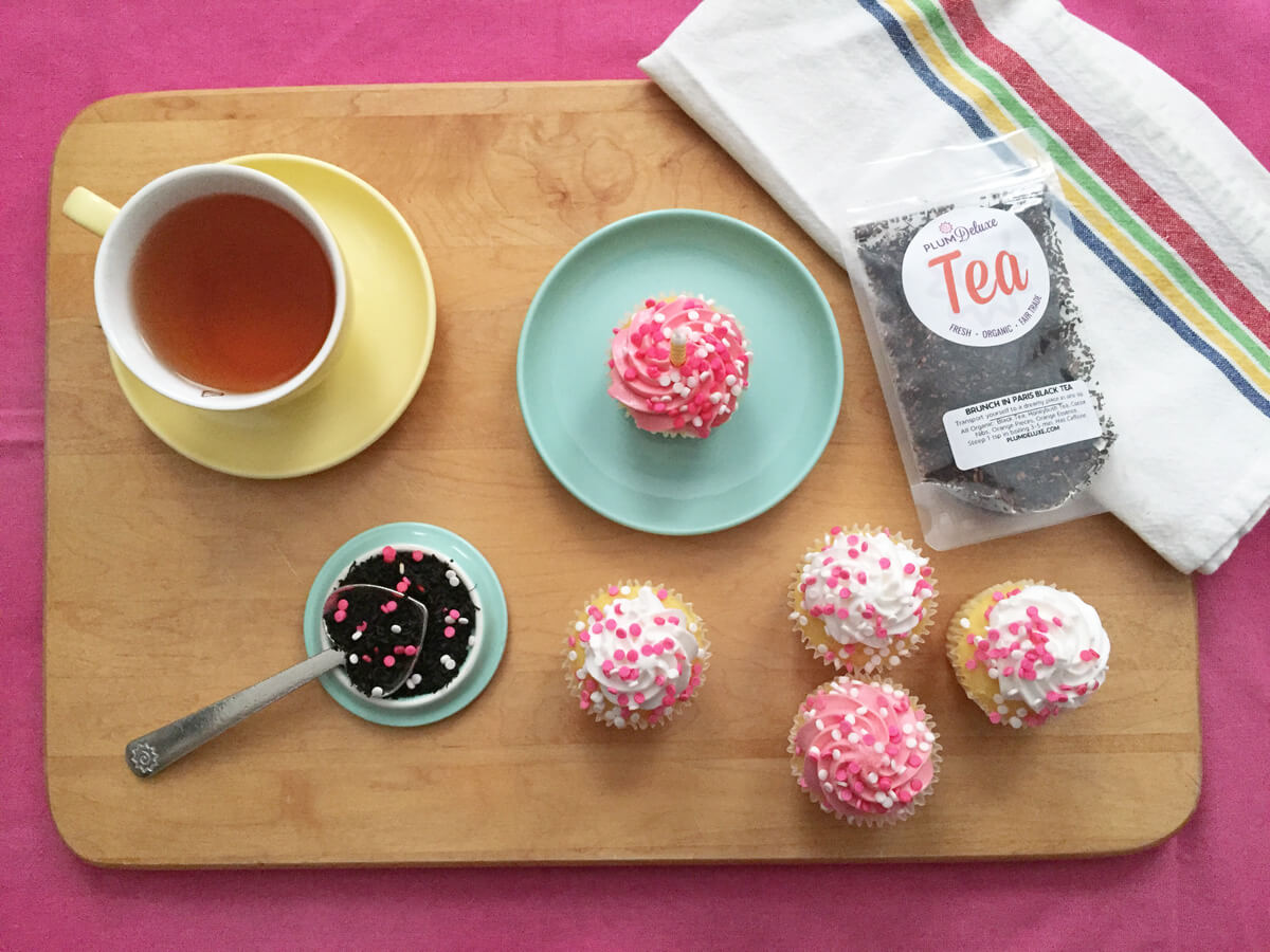 overhead view of cupcakes with pink and white icing on a blue plate, a yellow cup of tea, and Plum Deluxe loose leaf tea on a wooden board.