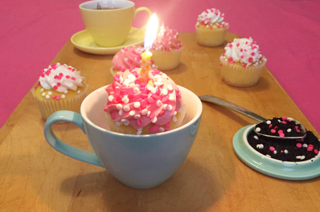 closeup of a cupcake with pink and white frosting and a lit candle in a blue teacup. more cupcakes, teacups, and Plum Deluxe loose leaf tea are in the background.