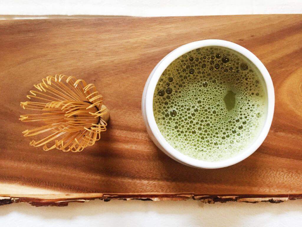 overhead view of a cup of matcha green tea with chasen matcha whisk.