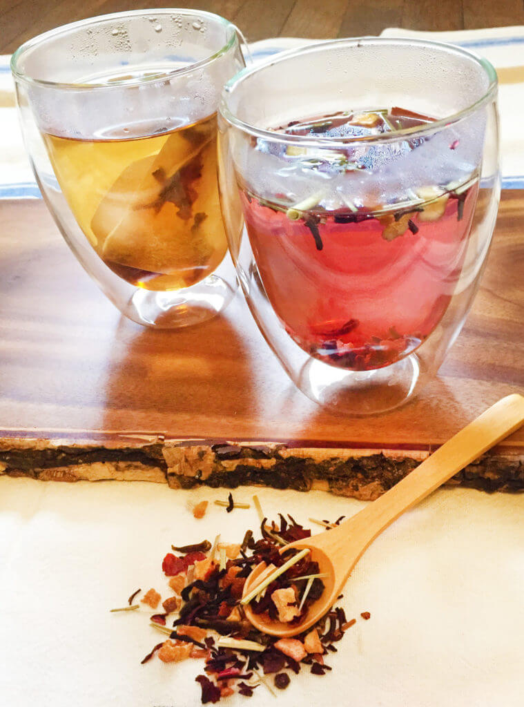 two glasses of iced loose leaf tea rest on a wooden board behind a spoonful of tea leaves.