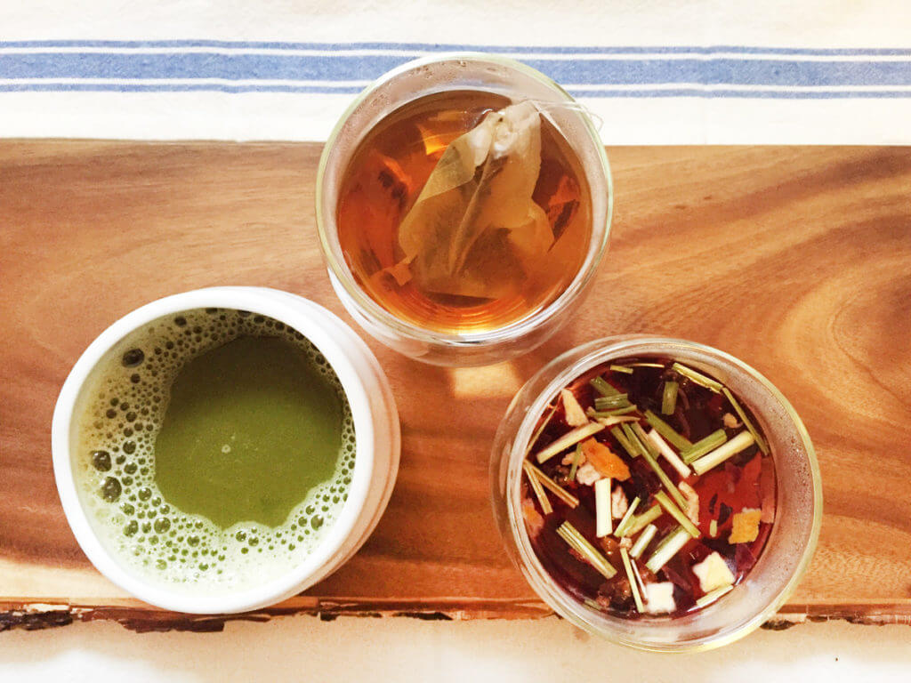 overhead view of three cups of loose leaf tea and matcha green tea.
