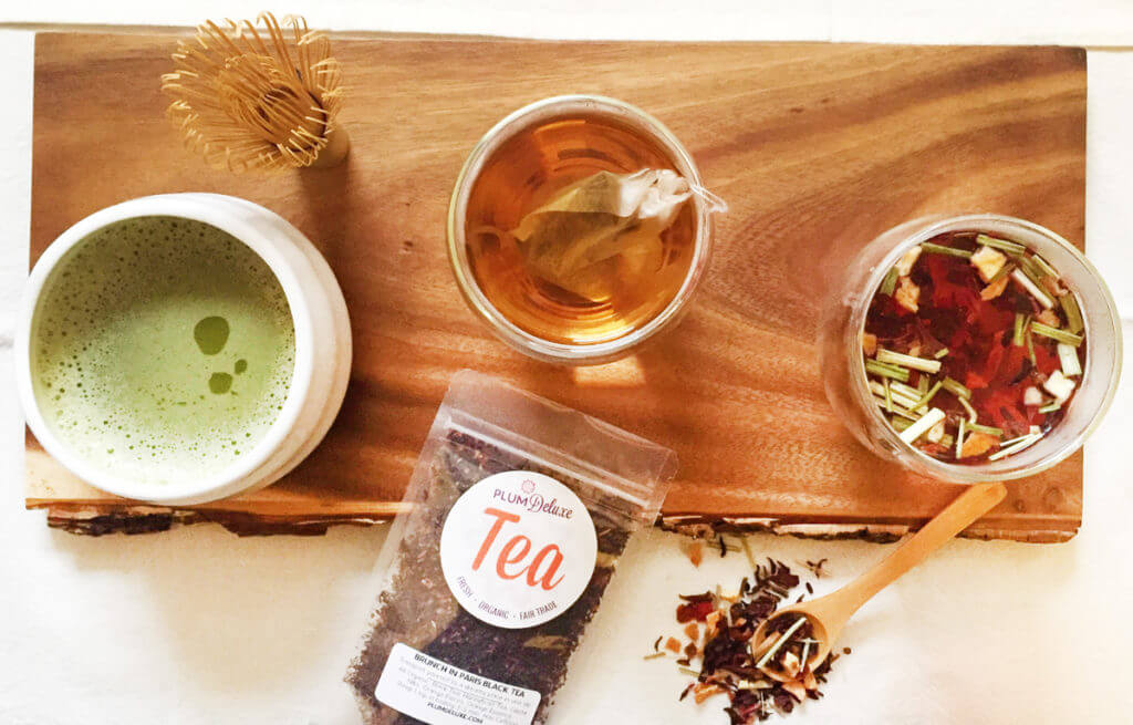 Overhead view of loose leaf tea brewing in several cups, a cup of matcha and a whisk, and a bag of tea on a wooden board.