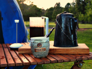 A cast iron kettle, french press, and mug sit on a wooden table at a camp site.