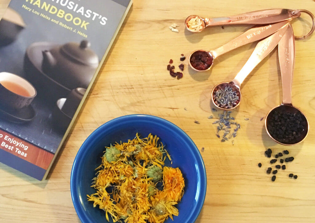 Overhead view of rose gold measuring spoons with various herbs and spices, a blue bowl of yellow calendula petals, and a book about tea on a wooden surface.