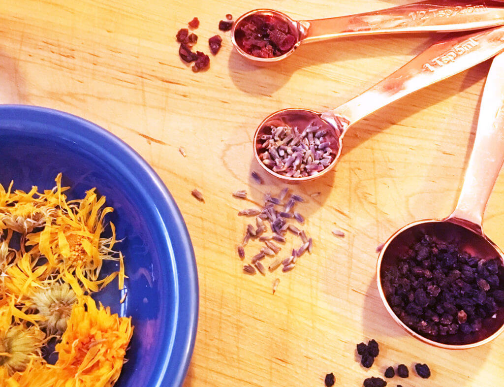 Overhead view of rose gold measuring spoons with various herbs and spices and a blue bowl of yellow calendula petals on a wooden surface.