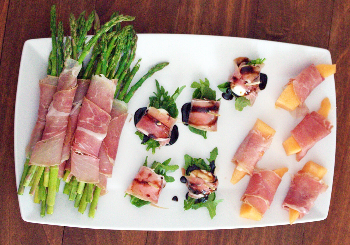 Overhead view of three easy prosciutto appetizers – prosciutto with asparagus, mozzarella, and melon – on a white platter.