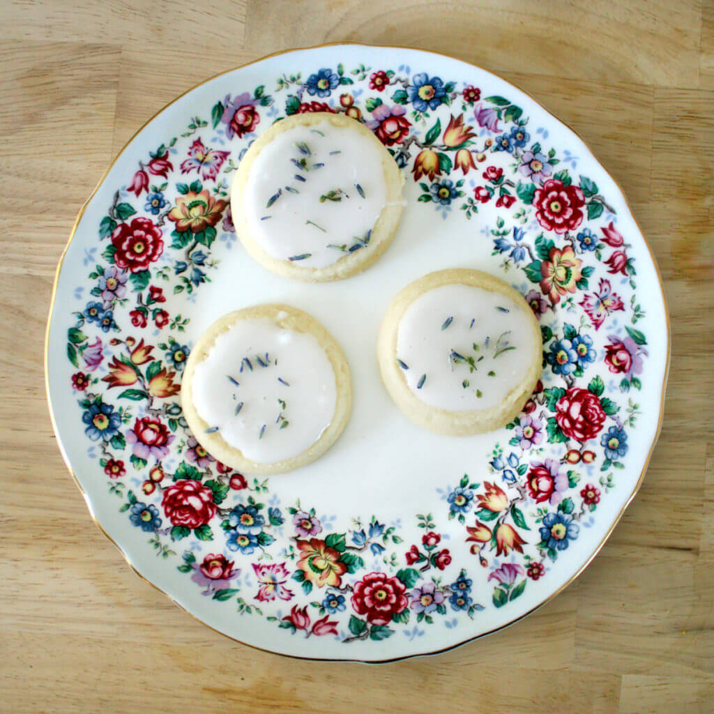 overhead view of three tea cookies with icing on a pretty floral plate.