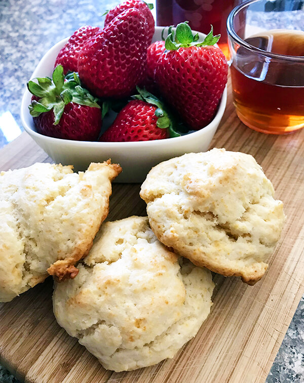 Cream shortcake biscuits sit on a wooden board, with a bowl of fresh strawberries and a cup of sugar plum tea syrup in the background.