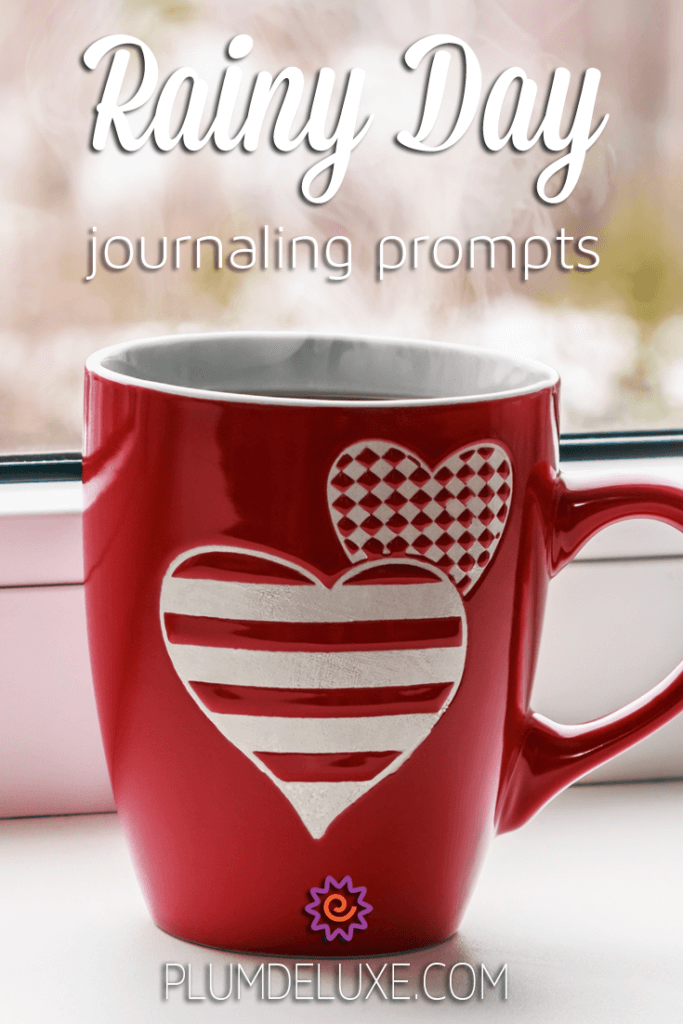 "A red mug with white striped hearts sits on a windowsill with the words ""Rainy Day Journaling Prompts"""