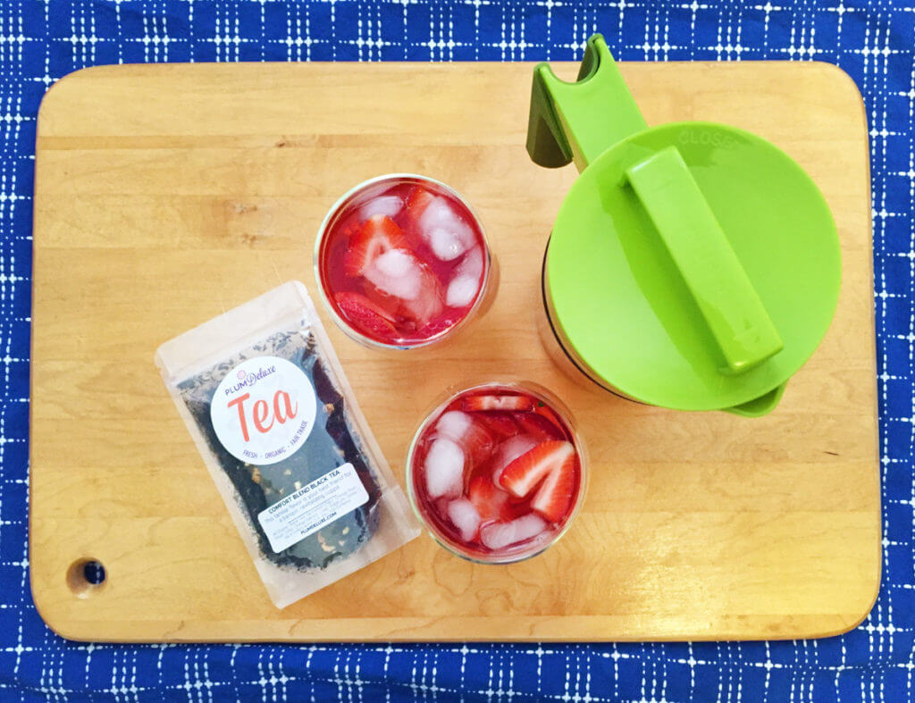 An overhead view of two glasses of red iced tea with a green iced tea pitcher and package of Plum Deluxe loose leaf tea on a wooden background.