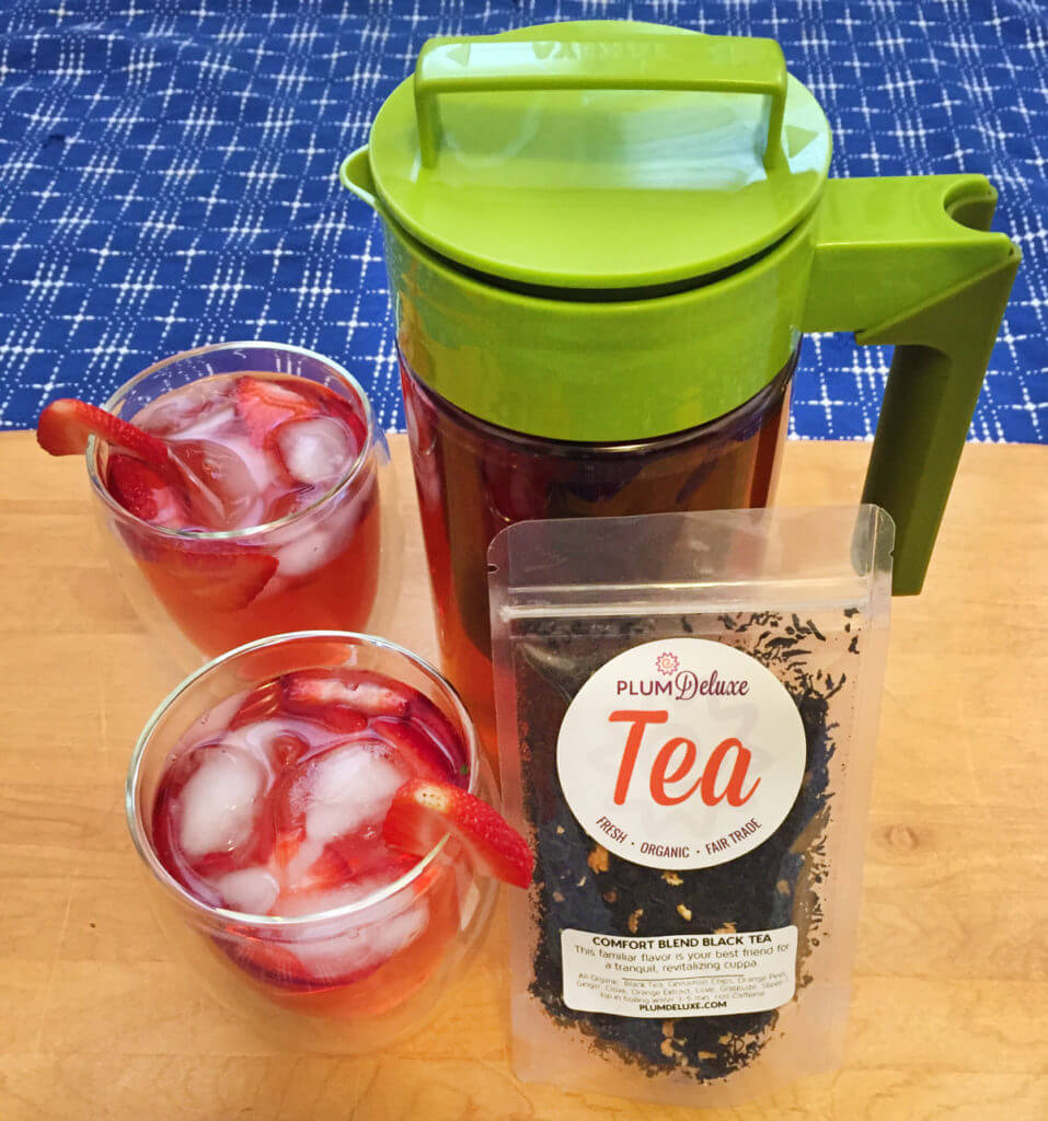 side view of two glasses of red iced tea, a green iced tea pitcher, and a bag of Plum Deluxe loose leaf tea on a wooden background with blue tablecloth.