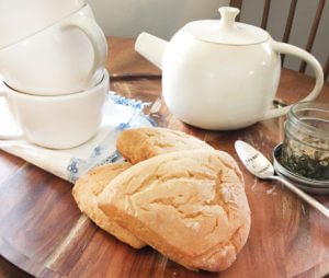 "A white teapot and teacups, scones, loose leaf tea, and a silver spoon that says ""Curiouser and Curiouser"" are laid out on a wooden table."