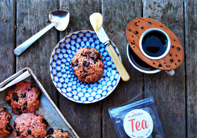 Overhead view of baked scone cookies and a cup of loose leaf tea.