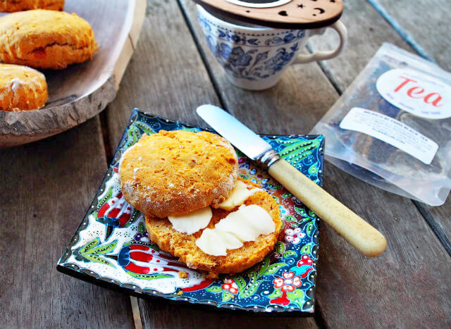 A split sweet potato scone is slathered in butter and served with a cup of tea.